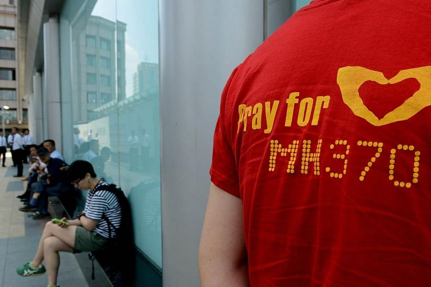 Chinese relatives of passengers from the missing Malaysia Airlines flight MH370 gather outside the building housing the Malaysian Airlines office in Beijing on June 11, 2014.Police have identified possible suspects who made unauthorised withdra