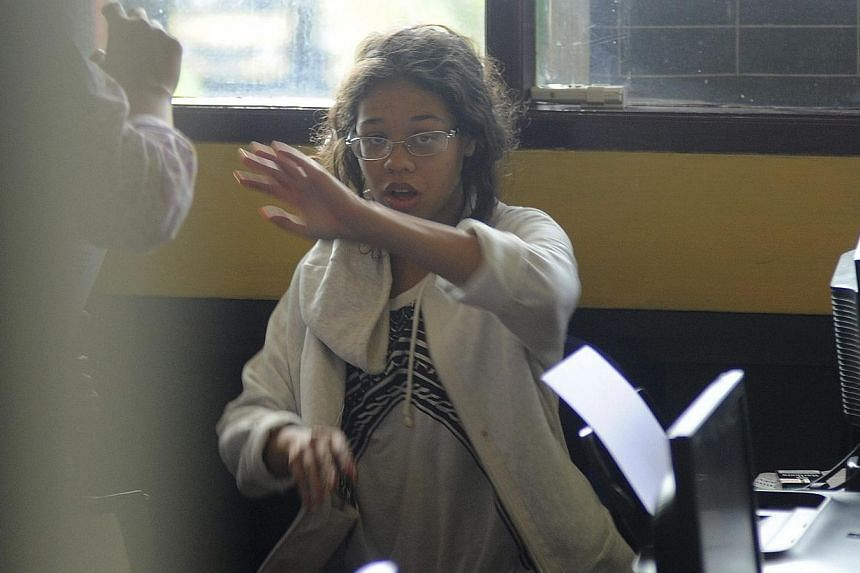 Heather Mack, the daughter of an American woman found dead inside a suitcase on the Indonesian holiday island of Bali, gestures while in custody in a police station in Denpasar on Aug 14, 2014.Indonesian police on Thursday, Aug 14, 2014, ran ps