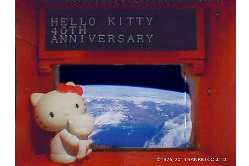 A 4-cm tall Hello Kitty figurine placed under a scrolling display in front of a window of the Hodoyoshi-3 satellite, is seen in what Sanrio said is a still image from a video, made available to Reuters on Aug 14, 2014. Hello Kitty, Japan's ambassador