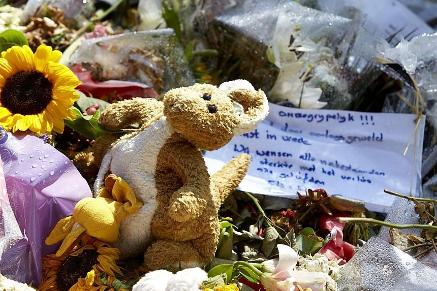 Flowers and stuffed animals are left in memory of the victims of Malaysia Airlines flight MH17 at the Korporaal van Oudheusdenkazerne in Hilversum, where the identification process of the victims is taking place on Aug 3, 2014. Malaysia has decl