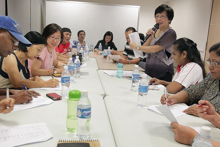 Madam Manuel Stella Consearo (far right), 63, is one member of the group of about 30 participants learning basic conversational Hokkien under the guidance of Madam Ng Lay Geok (standing), 71, at the Nee Soon South Community Club.