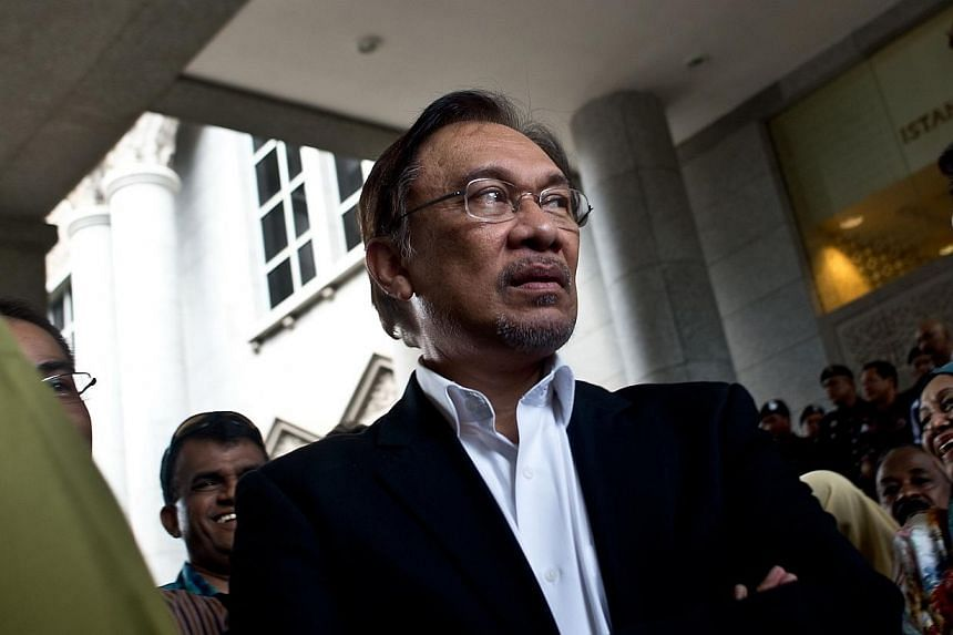 This file picture taken on March 7, 2014 shows Malaysian opposition leader Anwar Ibrahim waiting for his car outside the federal courts in Putrajaya.Malaysia's highest court on Thursday set a late October hearing date for opposition leader An