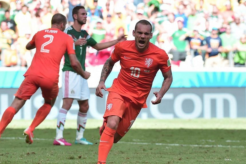 Netherlands' midfielder Wesley Sneijder (right) celebrates after scoring to make it 1-1 during a Round of 16 football match between the Netherlands and Mexico at Castelao Stadium in Fortaleza during the 2014 FIFA World Cup on June 29, 2014. His goal