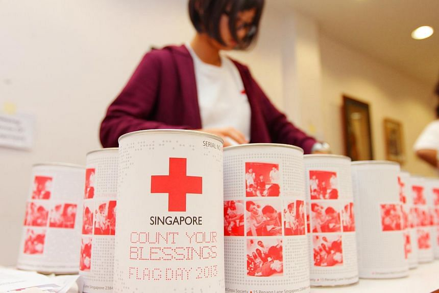 A Singapore Red Cross volunteer organizing the donation tins to be used on its Flag Day held on Jan 26, 2013. The amount of donations to charity last year hit $970 million - about 6 per cent less than the record $1.031 billion raised in 2012. --