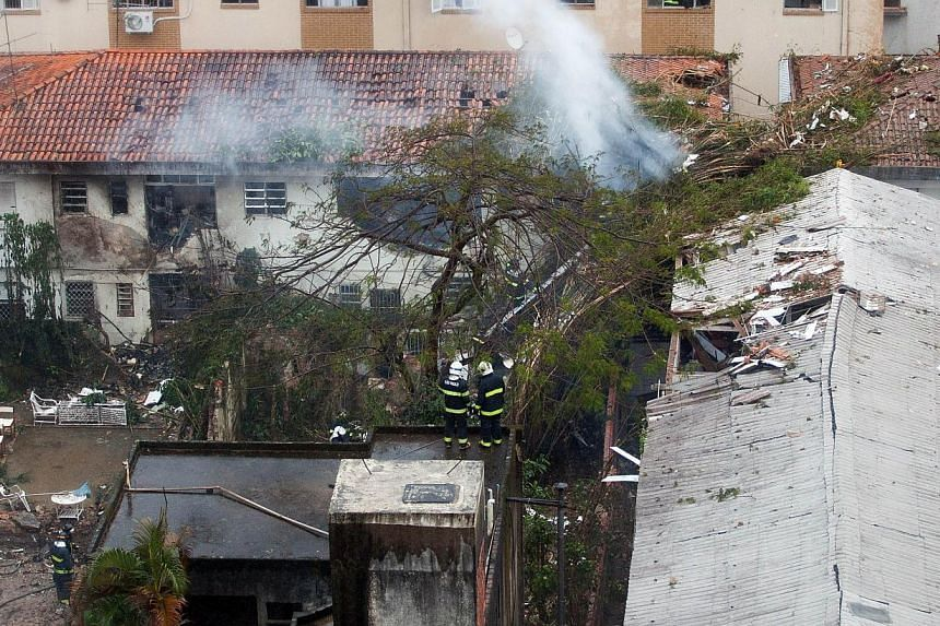 Rescuers work at the site of the crash of the Cessna 560XL aircraft carrying the presidential candidate of the Brazilian Socialist Party Eduardo Campos in Santos, Sao Paulo state, Brazil, on August 13, 2014. The plane failed to land and crashed into