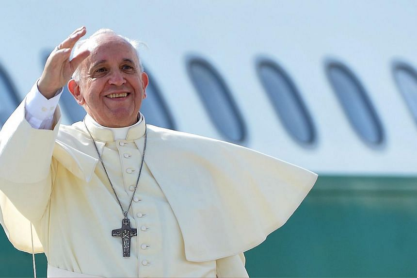 Pope Francis waves from the top of the stairs leading to the plane that will carry him to the South Korea, at Rome's Fiumicino international airport on Aug 13, 2014. -- PHOTO: AFP