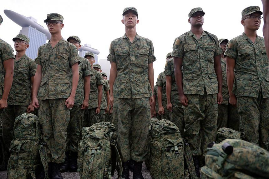 Recruits stand at attention during their Basic Military Training (BMT) during the Passing Out Parade held at the Floating Platform@Marina bay on April 12, 2014. -- ST PHOTO: MARK CHEONG