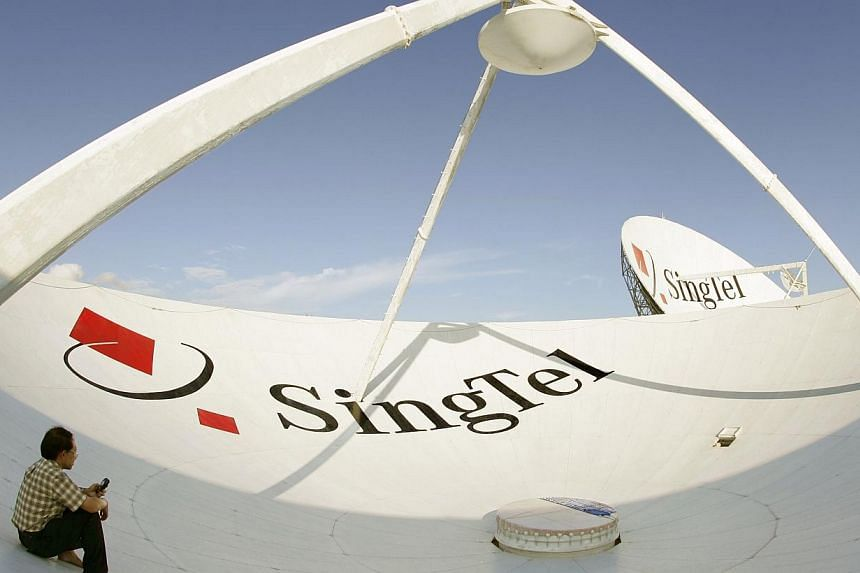 A Singapore Telecommunications Ltd. employee uses his mobile phone while sitting inside one of the company's giant satellite dishes shortly after periodic work to clean it was completed in Singapore on Monday, July 19, 2004.Singapore Telecommun