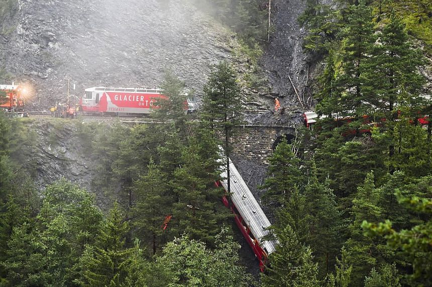 Rescuers work near a train after it was derailed by a landslide near Tiefencastel, in a mountainous part of eastern Switzerland, on Aug 13, 1014. -- PHOTO: AFP