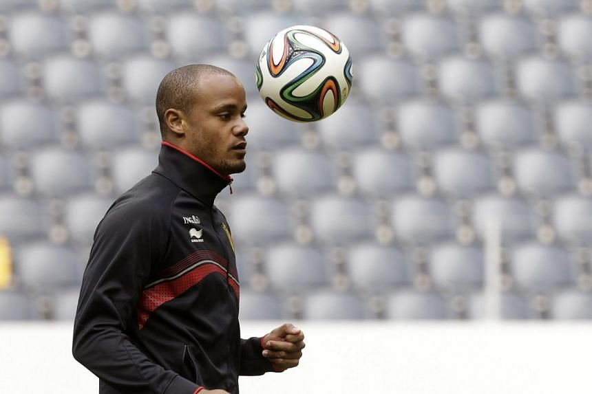 Vincent Kompany controlling a ball during a training session ahead of the 2014 World Cup, in Stockholm in May. Kompany has signed a new five-year contract with English Premier League champions Manchester City, it was announced on Wednesday. -- PHOTO: