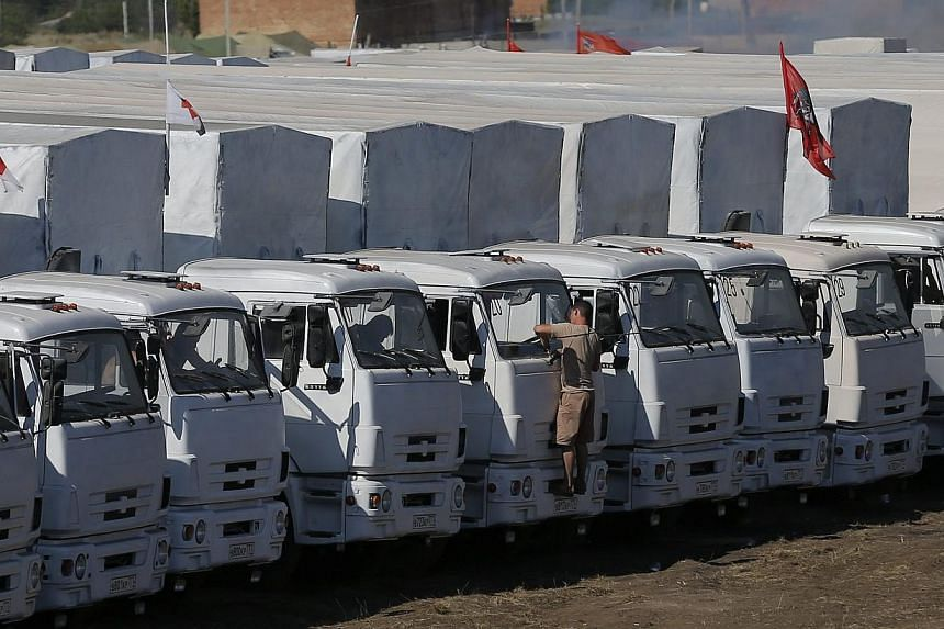 """A Russian convoy of trucks carrying humanitarian aid for Ukraine is parked at a camp near Kamensk-Shakhtinsky, Rostov Region on Aug 15, 2014.Ukrainian officials were preparing to inspect a massive Russian """"aid"""" convoy bound for the conflict-tor"""