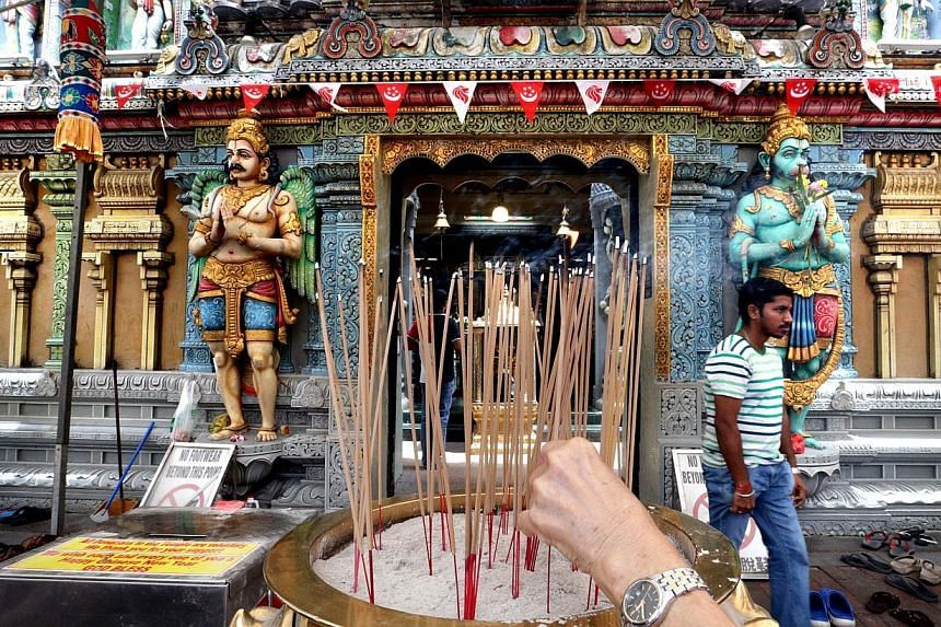 (Above) Besides Hindu worshippers, the Sri Krishnan Temple in Waterloo Street also sees devotees from the Chinese temple next door stopping by to light joss sticks (left) and say quiet prayers. (Far left) Crowds thronging the 130-year-old Kwan Im Tho