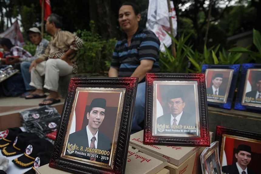 A vendor selling portraits of President-elect Joko Widodo and his running mate Jusuf Kalla in Jakarta after last month's election. Expectations are high that Mr Joko will be able to peacefully push through necessary reforms. -- PHOTO: REUTERS