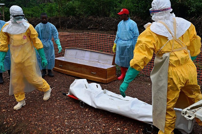 Medicins Sans Frontieres (MSF) medical workers wearing protective clothing carry the body bag of an Ebola victim at the MSF facility in Kailahun, on Aug 14, 2014.Staff with the World Health Organisation battling an Ebola outbreak in West Africa