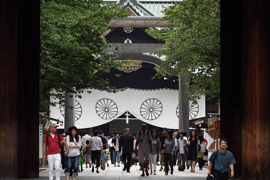 People visit the controversial Yasukuni Shrine in Tokyo on Aug 14, 2014, one day before the 69th anniversary of Japan's surrender in World War II. -- PHOTO: AFP