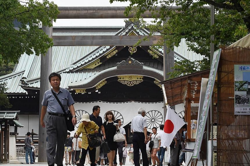People pray and make offerings as they visit the controversial Yasukuni Shrine in Tokyo on Aug 14, 2014, one day before the 69th anniversary of Japan's surrender in World War II. -- PHOTO: AFP