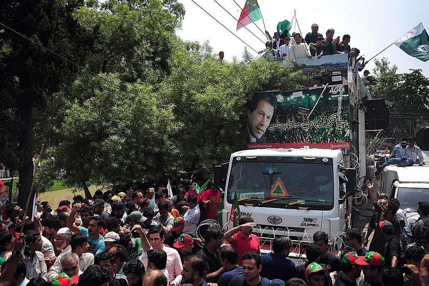 Pakistan cricketer-turned-politician Imran Khan (top, centre) heads a protest march from Lahore to Islamabad against the government, in Lahore on August 14, 2014. Thousands of protesters gathered in the Pakistani city of Lahore on August 14, preparin
