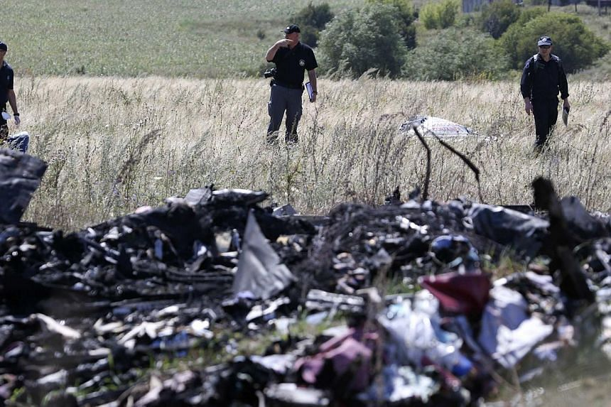 International experts investigating the site of downed Malaysia Airlines Flight MH17 in the Donetsk region, in eastern Ukraine on August 1, 2014. Dutch forensic experts have identified a total of 127 victims, with 20 new names being released to