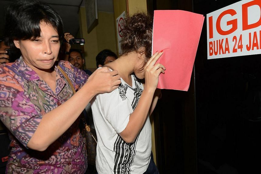 A policewoman escorts Heather Mack (right), suspected in the murder of her mother Sheila von Wiese Mack, while in custody at Bali police hospital in Denpasar on the Indonesian resort island of Bali on Aug 15, 2014. -- PHOTO: AFP