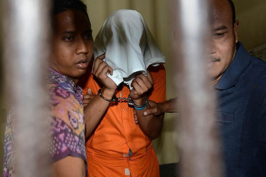 Police escort suspect Tommy Schaefer(centre), suspected in the murder of Sheila von Wiese Mack, while in custody at a holding cell at Bali police hospital in Denpasar on the Indonesian resort island of Bali on Aug 15, 2014. -- PHOTO: AFP