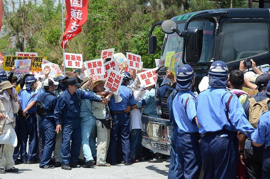 Protesters stage a rally at the gates of Camp Schwab, near the site of the new US military runways in Nago, Okinawa prefecture on August 14, 2014. Anti-military protesters rallied on and off shore on August 14 as work began as part of the long-stalle