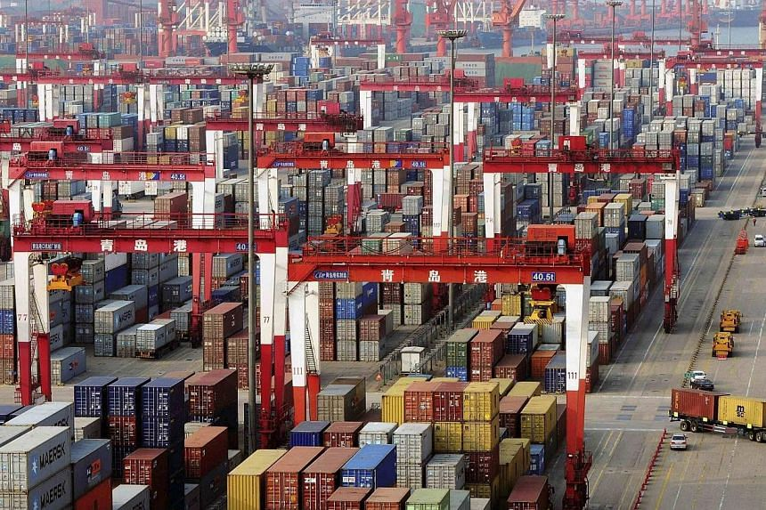 Trucks drive past piles of shipping containers at the Qingdao port in Qingdao, Shandong province on June 8, 2014. -- PHOTO: REUTERS