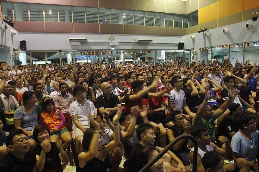 More than 300 football fans react when Germany scored its fourth goal against Portugal in a live screening of the World Cup at Sengkang Community Club on June 17, 2014. -- PHOTO: ST FILE
