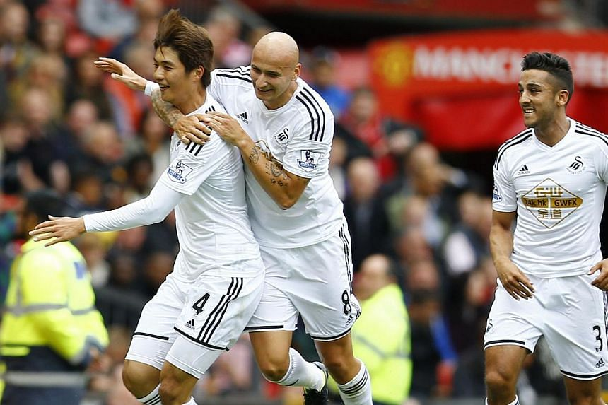 Swansea City's Ki Sung Yueng (left) celebrates with teammates Jonjo Shelvey (centre) and Neil Taylor after scoring a goal against Manchester United during their English Premier League match at Old Trafford on Aug 16, 2014. -- PHOTO: REUTERS