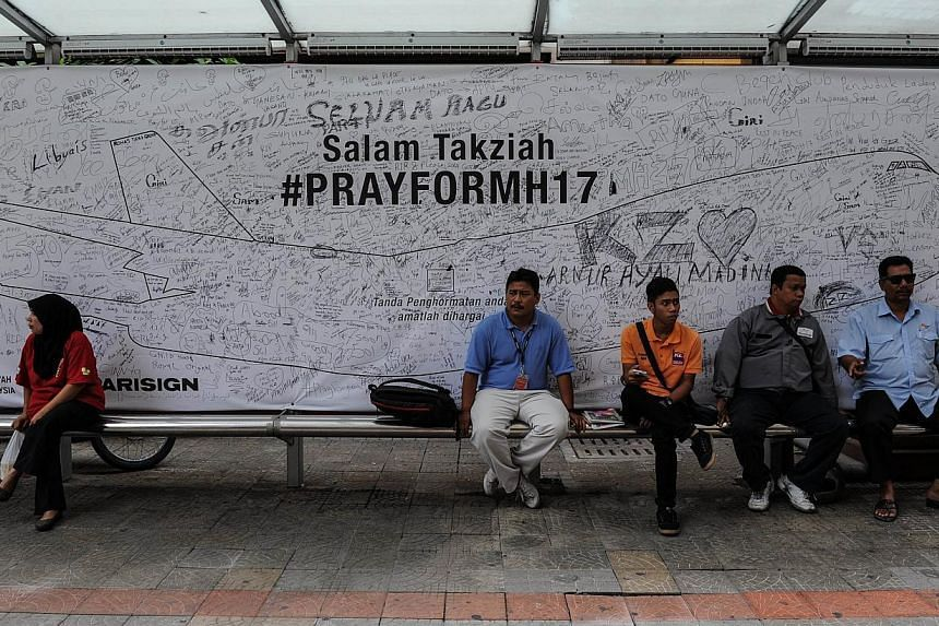 People sit in front a banner showing prayers and well-wishes for passengers onboard Malaysia Airlines flight MH17 that crashed in eastern Ukraine, at a bus stop in Kuala Lumpur on Aug 4, 2014. -- PHOTO: AFP