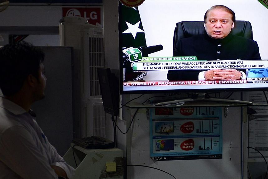 A Pakistani man listens to a broadcasted speech by Prime Minister Nawaz Sharif on a television in a electronics market in Islamabad on Aug 12, 2014.The leaders of two Pakistani protest movements vowed on Saturday to keep their protests alive un