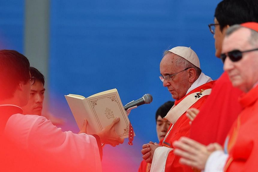 Pope Francis (centre) takes part in a beatification mass at Gwanghwamun Square in central Seoul on Aug 16, 2014. -- PHOTO: AFP