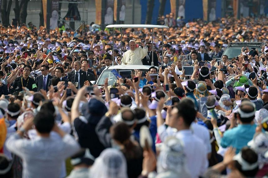 Catholic worshippers wave as Pope Francis (centre) arrives at Gwanghwamun Square in central Seoul on Aug 16, 2014. Atight security cordon was thrown around central Seoul on Saturday to screen out possible threats as up to one million peop