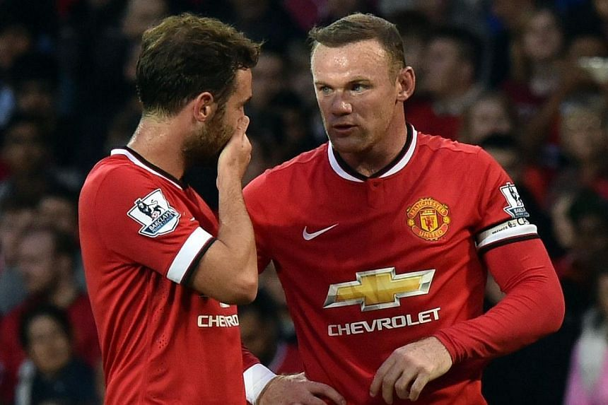 Manchester United's English striker Wayne Rooney (right) speaks to Spanish midfielder Juan Mata before taking a free kick during the pre-season football friendly match between Manchester United and Valencia at Old Trafford in Manchester. north west E