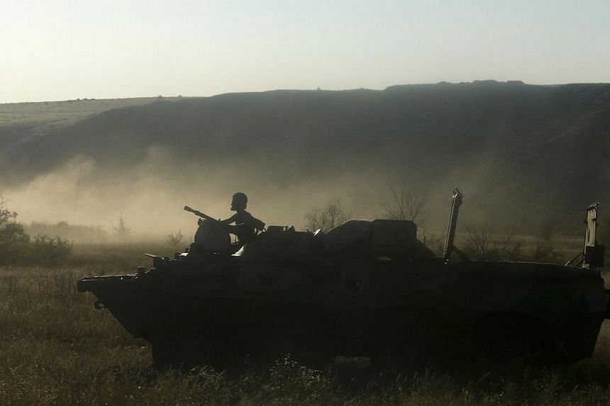A Russian serviceman rides atop an armoured personnel carrier (APC) through a field outside Kamensk-Shakhtinsky, Rostov Region, on Aug 15, 2014. Ukraine said on Friday it had destroyed part of a Russian armoured column that entered onto its territory