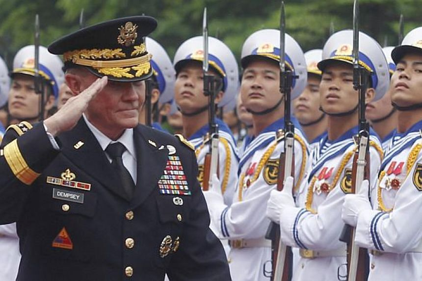 US Chairman of the Joint Chiefs of Staff General Martin Dempsey reviews the guard of honour during a welcoming ceremony at Vietnam's Defence Ministry in Hanoi on Aug 14, 2014. -- PHOTO: REUTERS