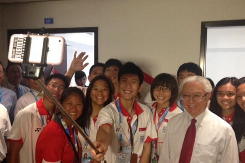 Team Singapore youth athletes take a selfie with President Tony Tan Keng Yam, after he visited their accommodation at the Youth Olympic Games Village. -- ST PHOTO: WALTER SIM