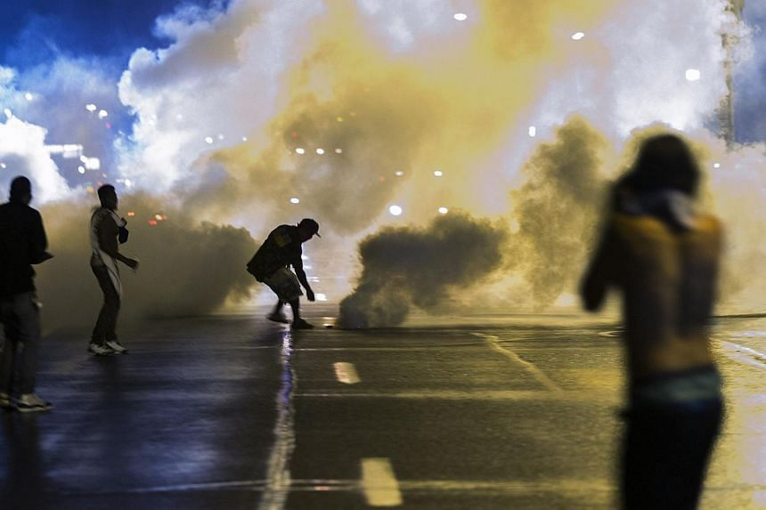 A protester reaches down to throw back a smoke canister as police clear a street after the passing of a midnight curfew meant to stem ongoing demonstrations in reaction to the shooting of Michael Brown in Ferguson, Missouri on Sunday, Aug 17, 2014.&n