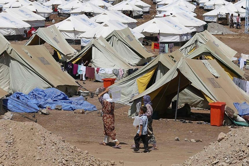 Refugees at Nowruz refugee camp,in Qamishli, north-eastern Syria,where displaced people from the minority Yazidi sect who fled the violence in the Iraqi town of Sinjar are seeking refuge, on Aug 16, 2014.Australia will offer to rese
