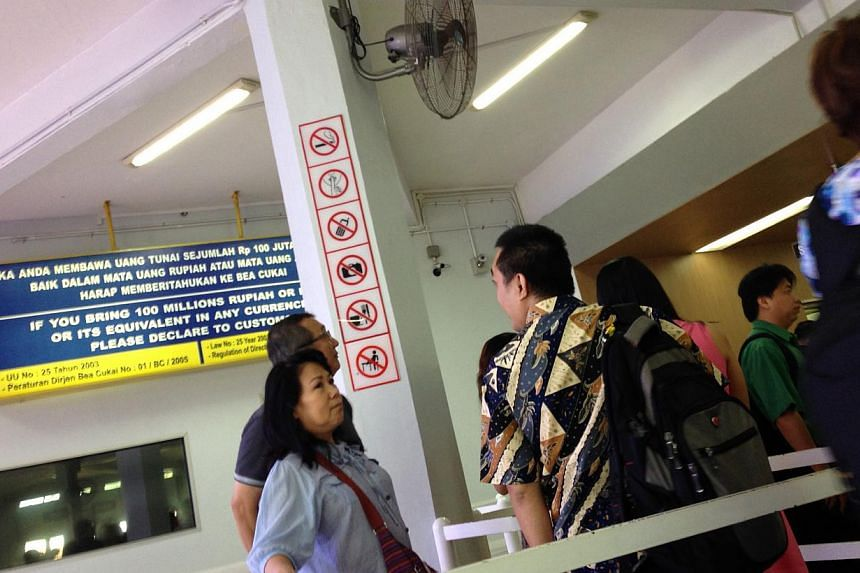Signs showing prohibited behaviour at the immigration checkpoint of the Batam Centre International Ferry Terminal are plastered all over the pillars. -- ST PHOTO: DANSON CHEONG