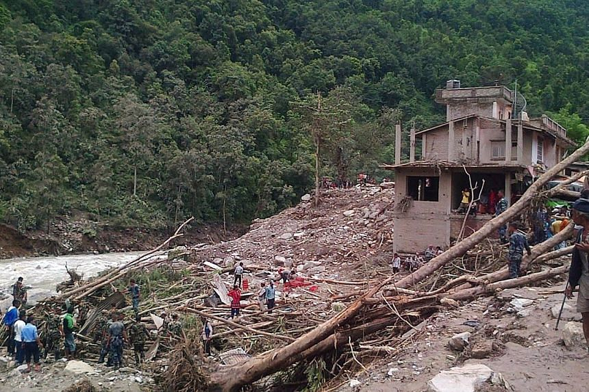 In this photograph taken using a cellphone, Nepalese residents and rescue personnel stand among debris at the site of a landslide on the Sukoshi river in Sindhupalchowk district northeast of Kathmandu on Aug 3, 2014. Rescuers in Nepal struggled