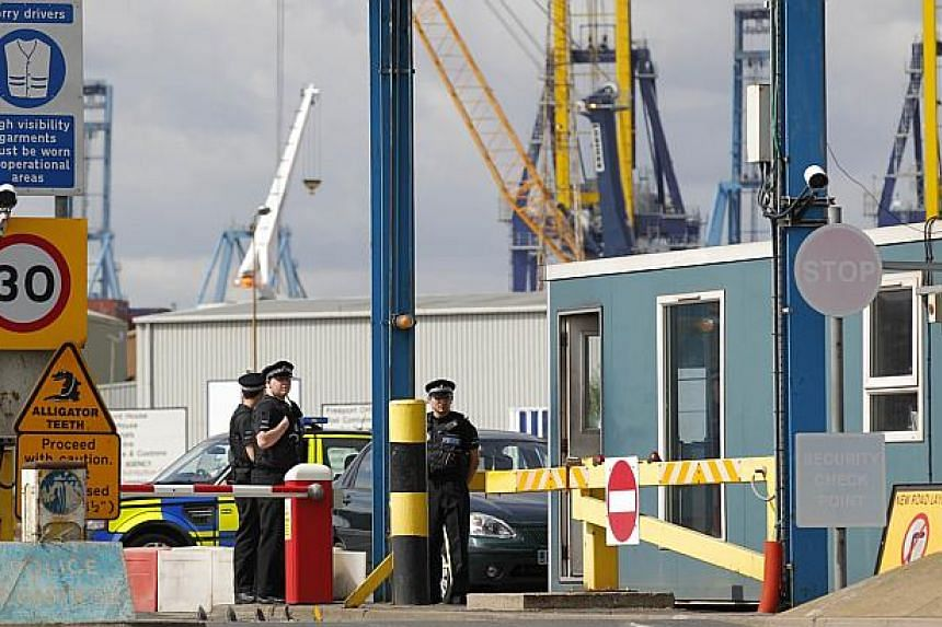 Police stand guard at an entrance to Tilbury Docks, east of London, on August 16, 2014, where one man was found dead and 34 men, women and children were found to be suffering from severe dehydration and hypothermia. Officers on Sunday said those in t