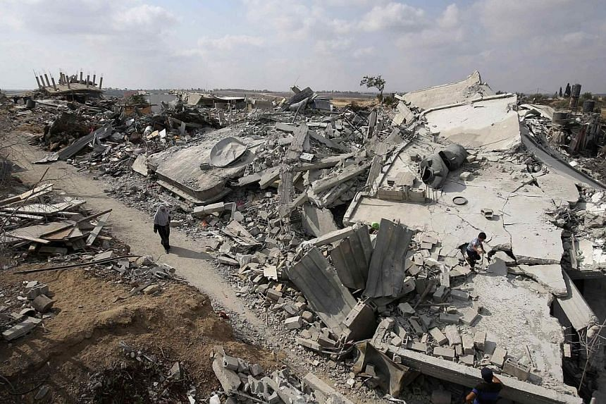 A Palestinian woman walks past the ruins of houses which witnesses said were destroyed during the Israeli offensive in Johr El-Deek village near the central Gaza Strip on Aug 17, 2014.The death toll in the war-torn Gaza Strip rose above 2,000 o