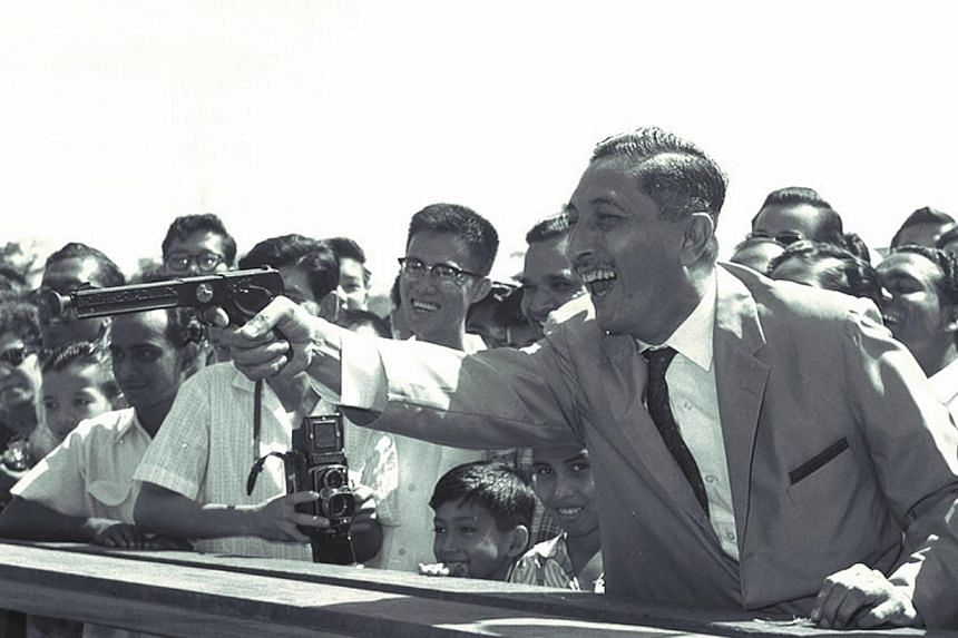 Mr Yusof Ishak taking aim at the shooting gallery after he officially opened the National Day Carnival on the grounds of Raffles Institution in 1960. -- PHOTO: ST FILE