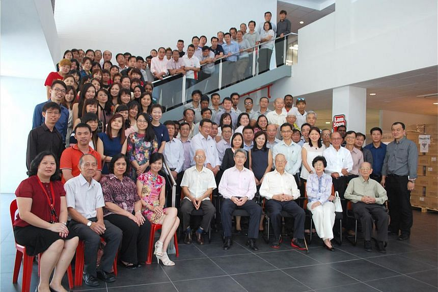Mr Whang Shang Ying (in pink shirt, front row) with his parents, Mr Whang Tar Liang and Madam Chen Mu Hsien on his left, and Lam Soon employees at a Chinese New Year gathering this year. -- PHOTO: COURTESY OF WHANG SHANG YING
