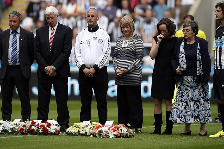 Relatives of Malaysia Airlines Flight MH17 victims Liam Sweeney and John Alder observe a minute's silence in their memory before Newcastle United's English Premier League soccer match against Manchester City at St James' Park in Newcastle upon Tyne,