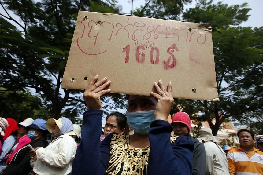 """A garment worker holds a placard reading """"Monthly minimum wage $160""""during a protest in central Phnom Penh in this December 31, 2013 file photo. Labour leaders behind the biggest strikes in Cambodia's US$5 billion (S$6.2 billion)garment i"""