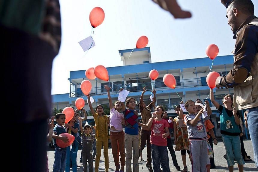 Palestinian children release red helium-filled balloons with notes of good will attached to them during an activity at a UN school in Jabalia in the northern Gaza Strip, where Palestinians who have been displaced by violence in Gaza have sought refug