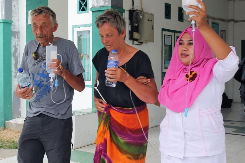 Survivor Jan van Ommen (left) of the Netherlands and fellow Dutch survivor Alice (centre, only first name available) are assisted by a nurse at a hospital in Sape, located on Indonesia's Sumbawa island on August 18, 2014 after being rescued two days