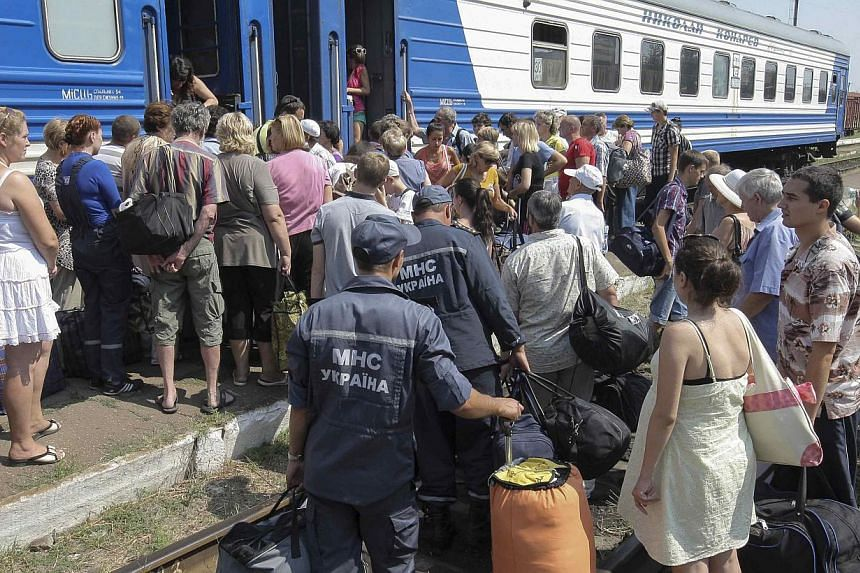 Refugees from the Luhansk region wait to board a train terminating in Kharkiv, at a railway station near the town of Svatovo on Aug 12, 2014.A convoy of buses carrying refugees from the east Ukrainian city of Luhansk was hit by rebel missile fi
