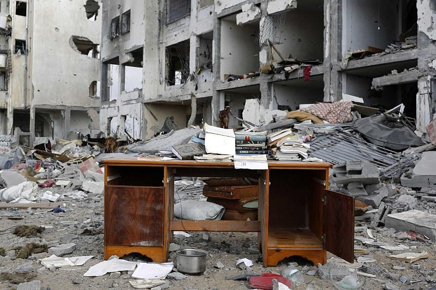 A desk sits amid the debris of buildings destroyed by what police said were Israeli airstrikes and shelling in the town of Beit Lahiya in the northern Gaza Strip on Aug 3, 2014. Israel on Tuesday, Aug 19, ordered a military air strike after thre